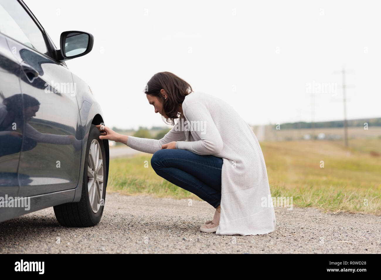 Woman checking car tyre during breakdown - Stock Image