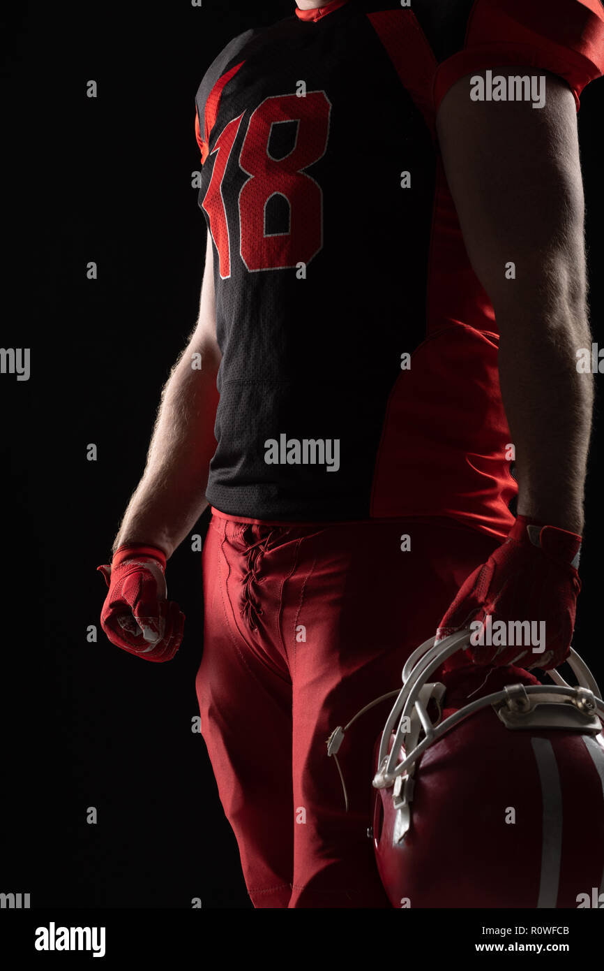 American football player standing with helmet against black background - Stock Image