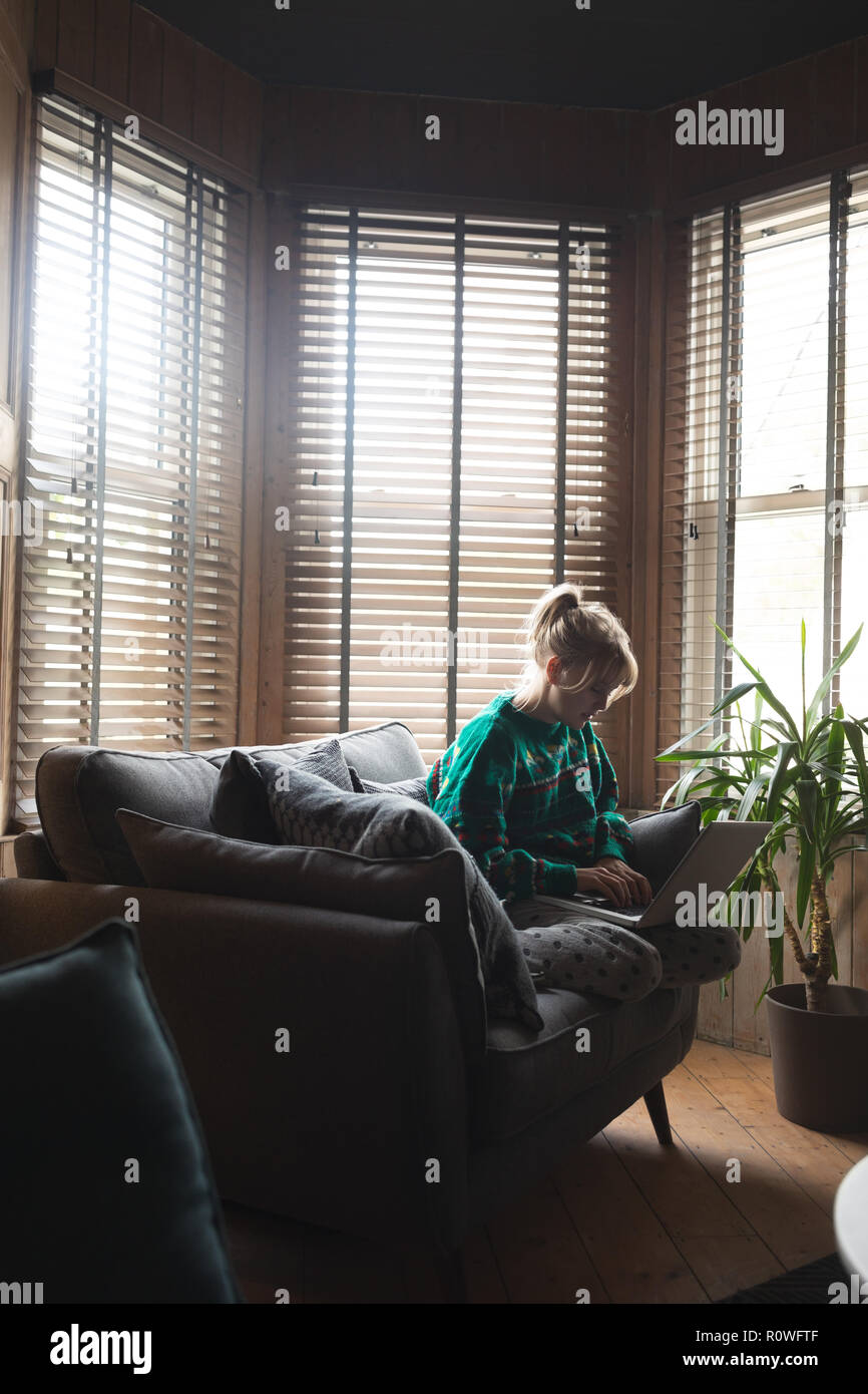 Woman using laptop in living room - Stock Image