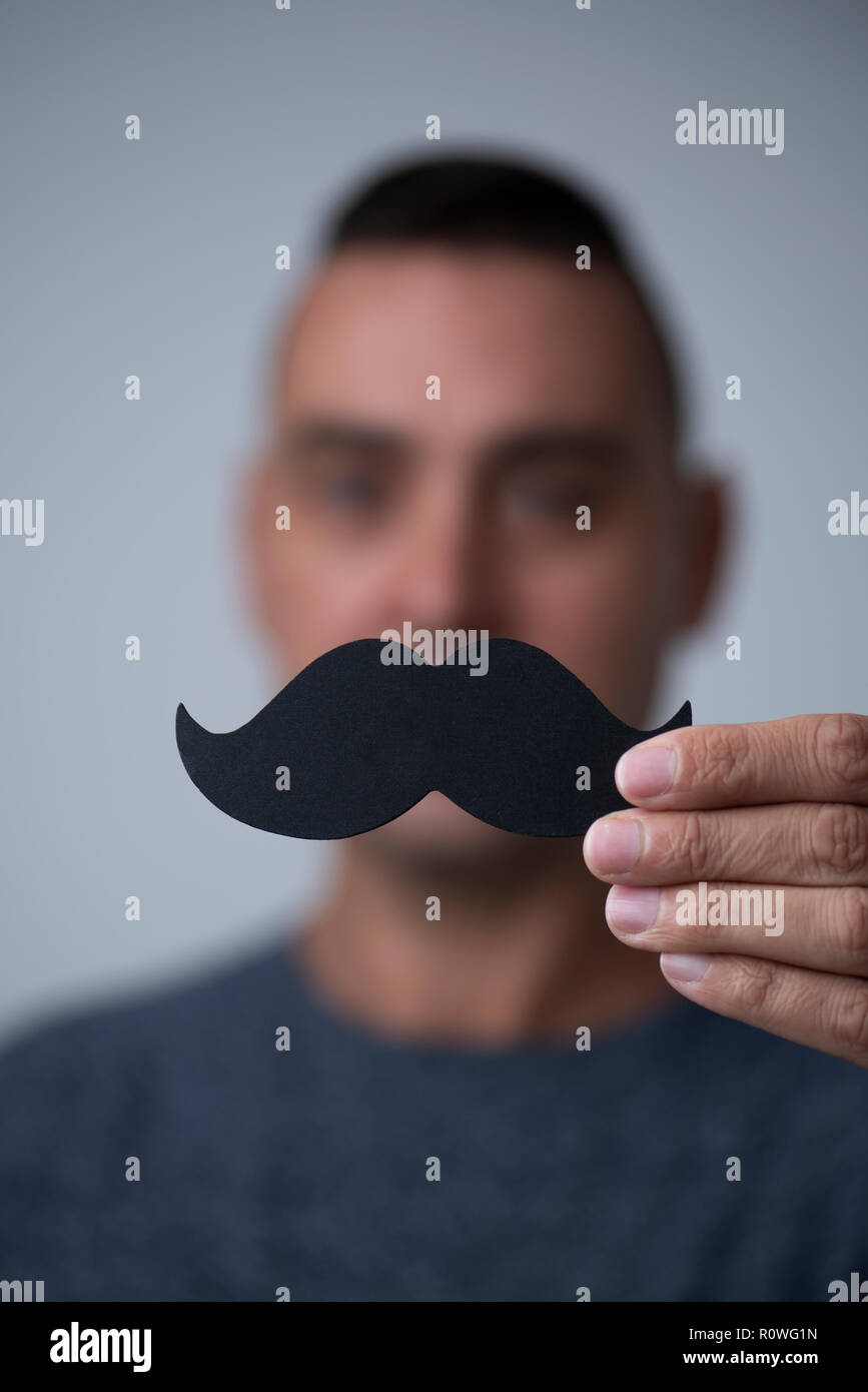 closeup of a young caucasian man holding a fake moustache in front of his face - Stock Image