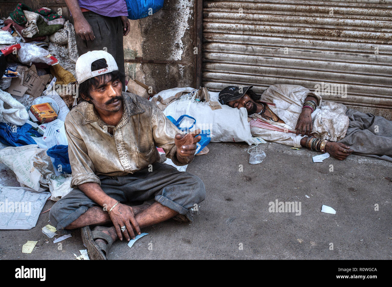 Drug addicts in a filth-strewn lane in the notorious Dongri area of Mumbai, India, mostly using a cheap heroin version called 'brown sugar' - Stock Image
