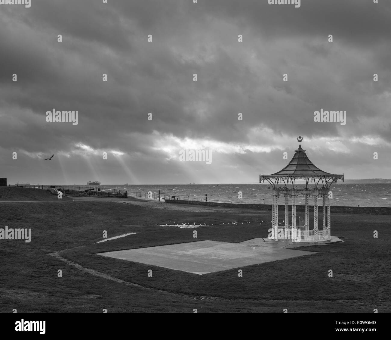Stormy Southsea Beach with light rays over the bandstand in black and white, Southsea, Portsmouth, Hampshire, UK - Stock Image