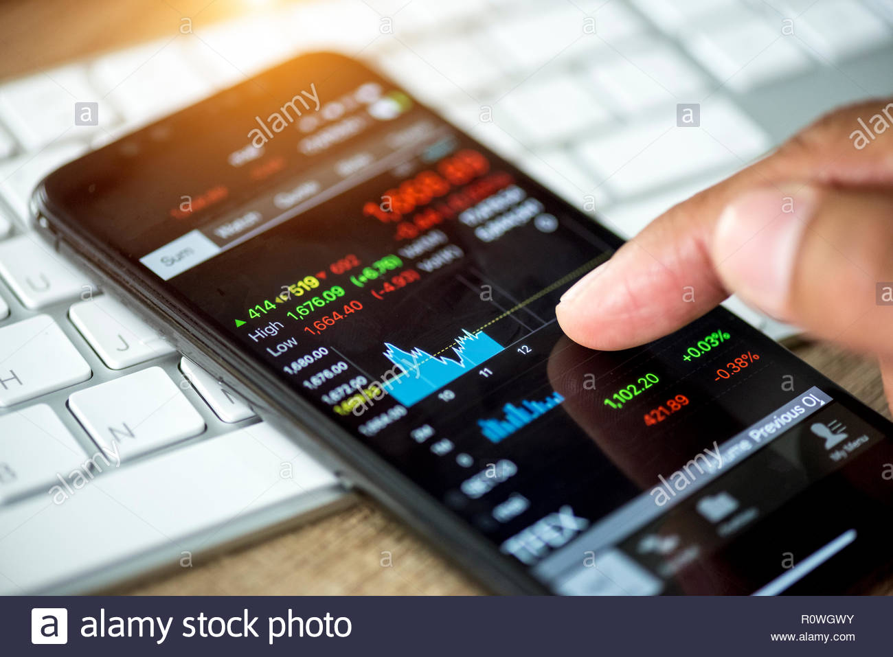 Businessman using mobile device check stock market data. - Stock Image