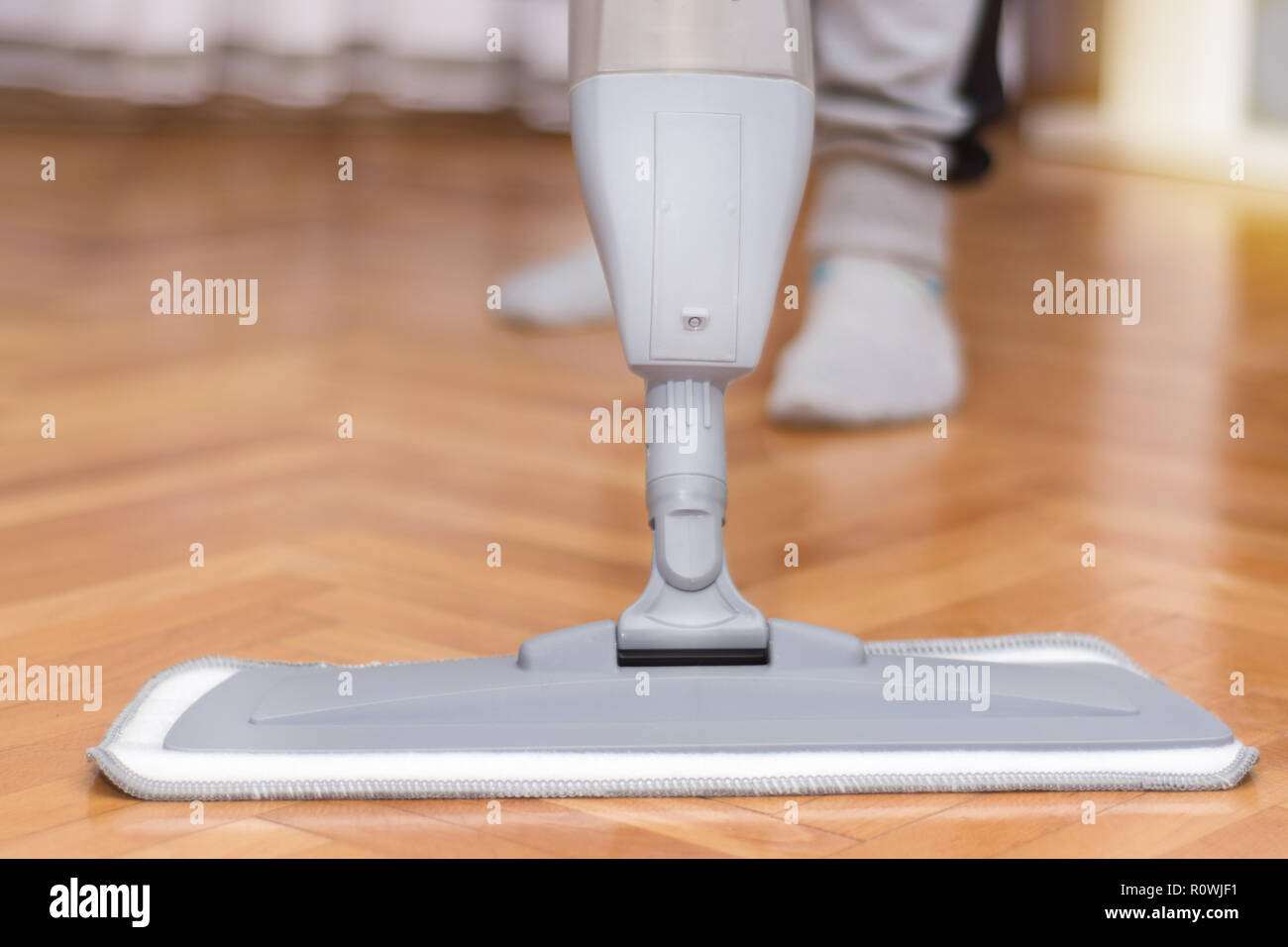 Women cleaning floor parquet with gray mop in morning at house. House work concept. Close up, selective focus - Stock Image