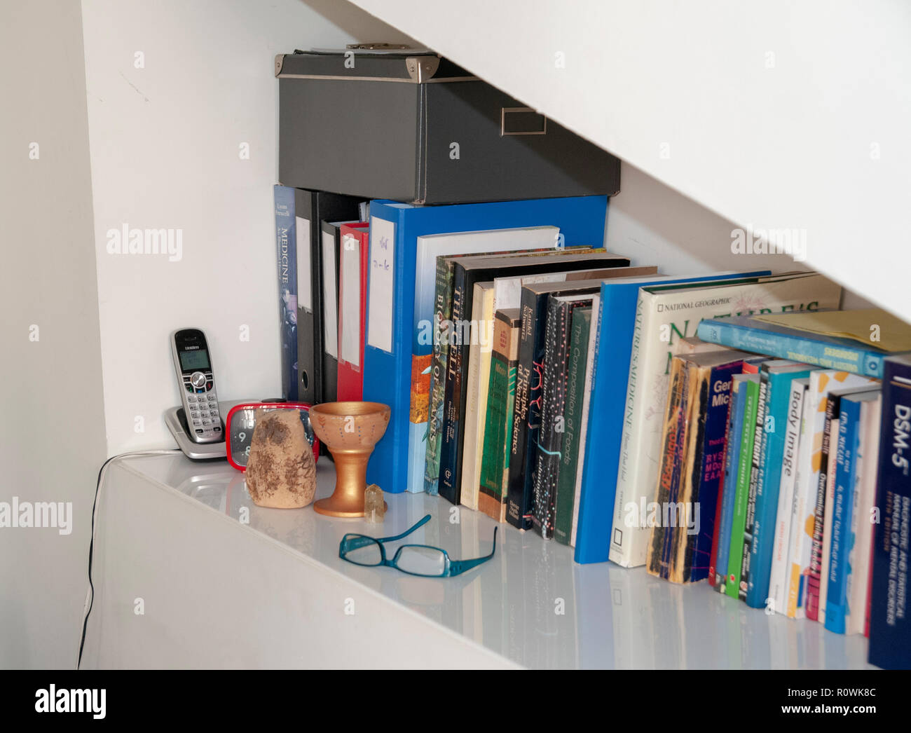 Bookshelf in a medical professional's consulting room - Stock Image