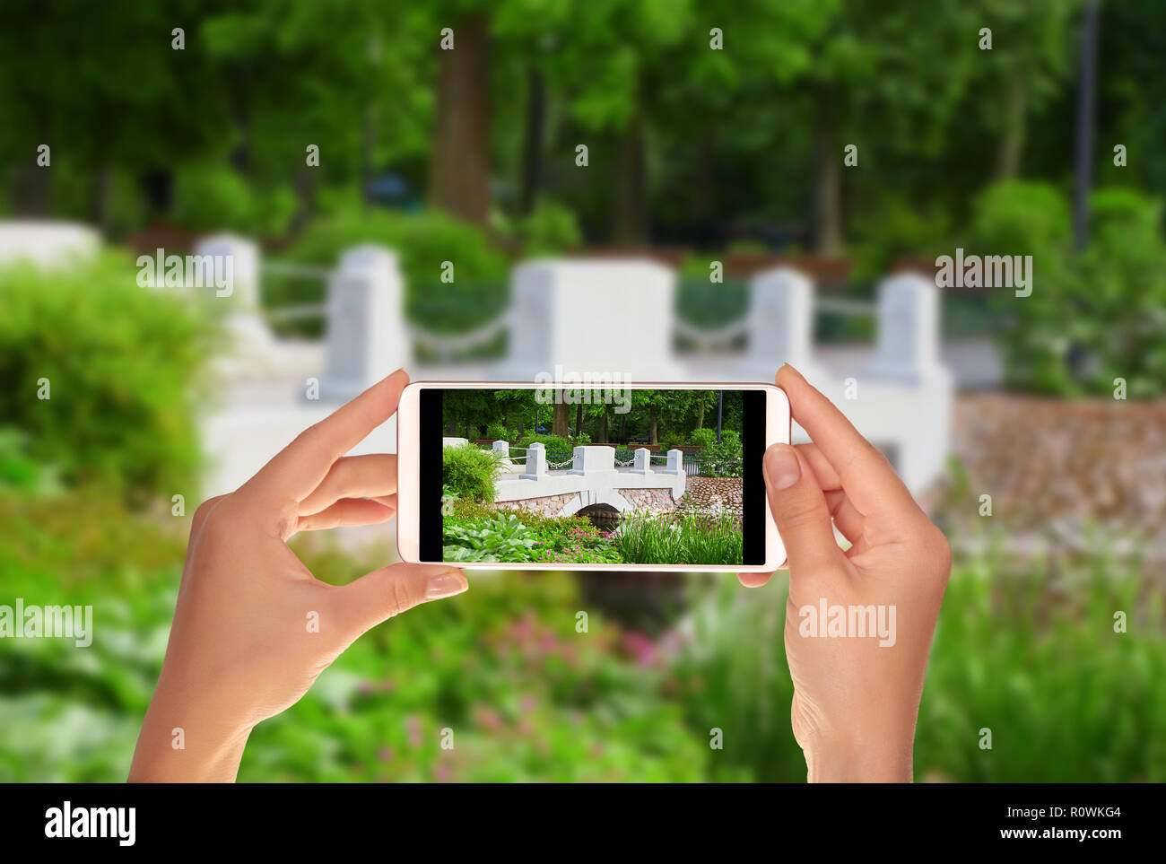 A tourist is taking a photo of bridge over river in the Bernardine Garden in Vilnius on a mobile phone Stock Photo