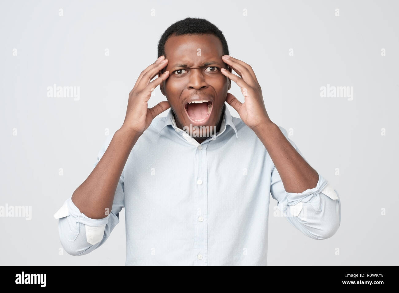 Annoyed african american man in blue shirt screaming in panic, shocked to hear bad news. Stressful situation concept. - Stock Image