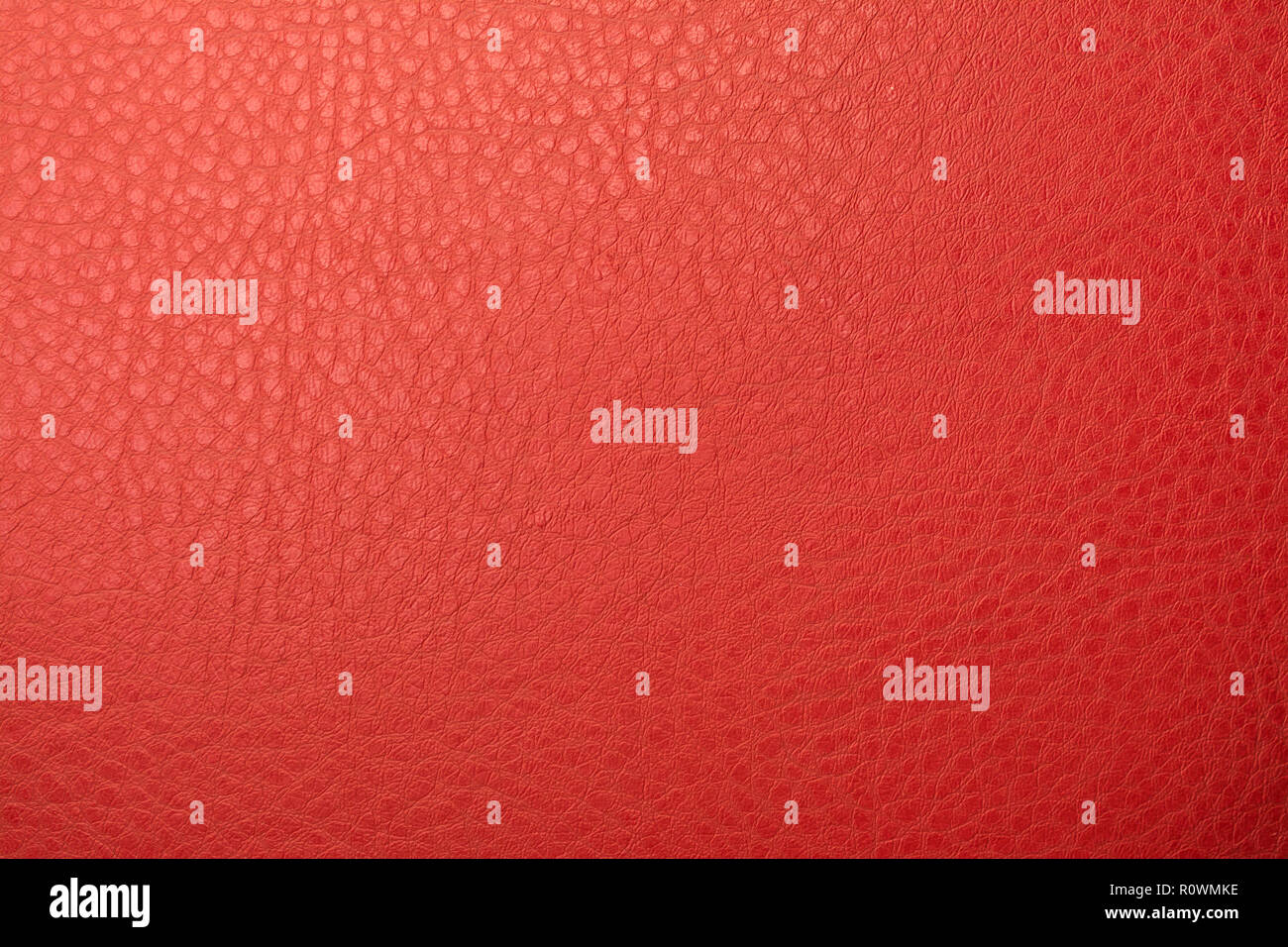 Red leather material texture background closeup - Stock Image