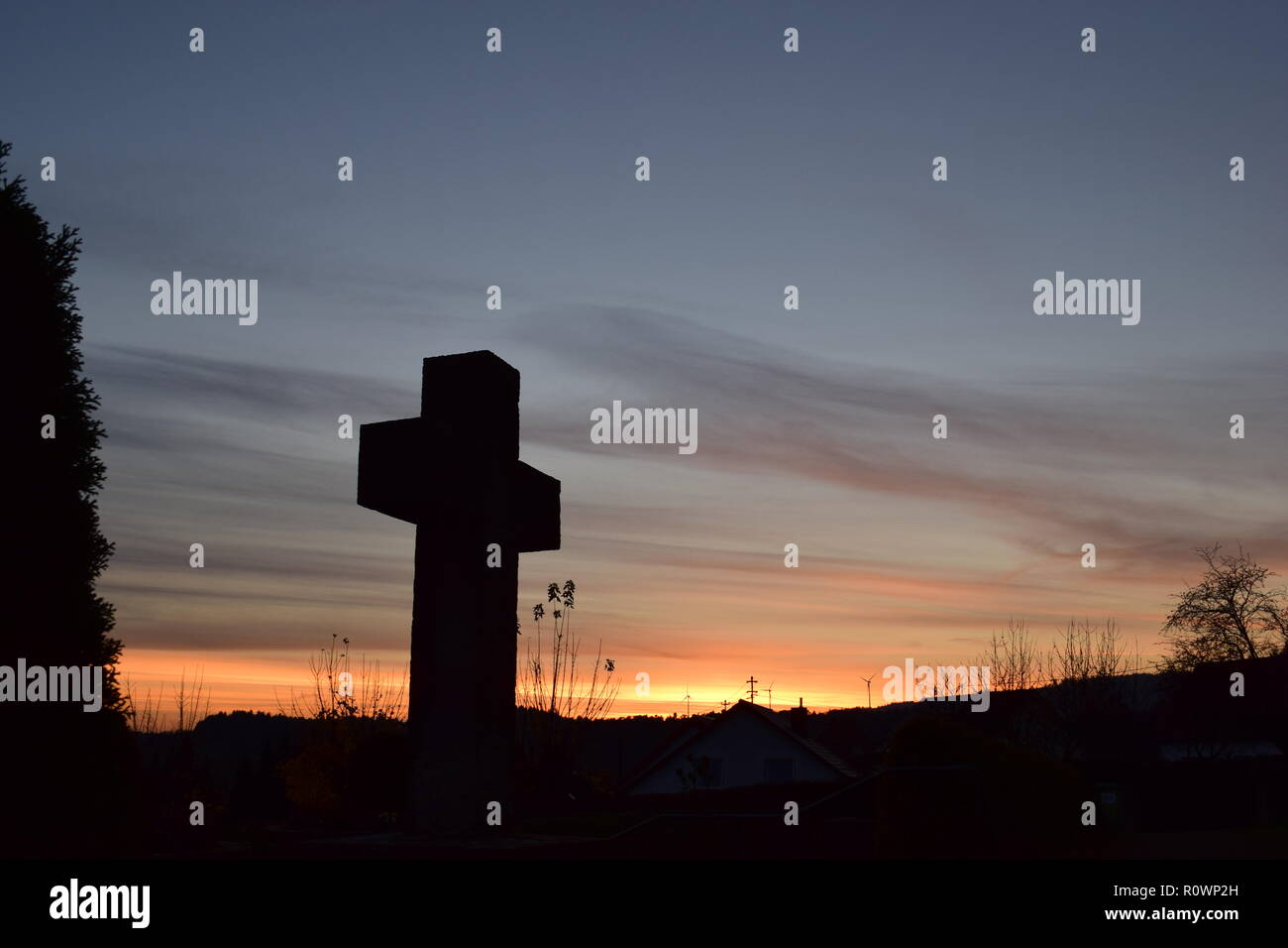 Timeline of the evening dusk sky viewed from behind a sand stone cross sculpture  during the sundown sun in the civil cemetery Reimsbach, Saarland, - Stock Image