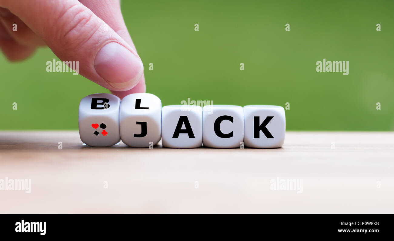 """Hand is turning a dice and changes the word """"Black"""" to """"Jack"""" Stock Photo"""