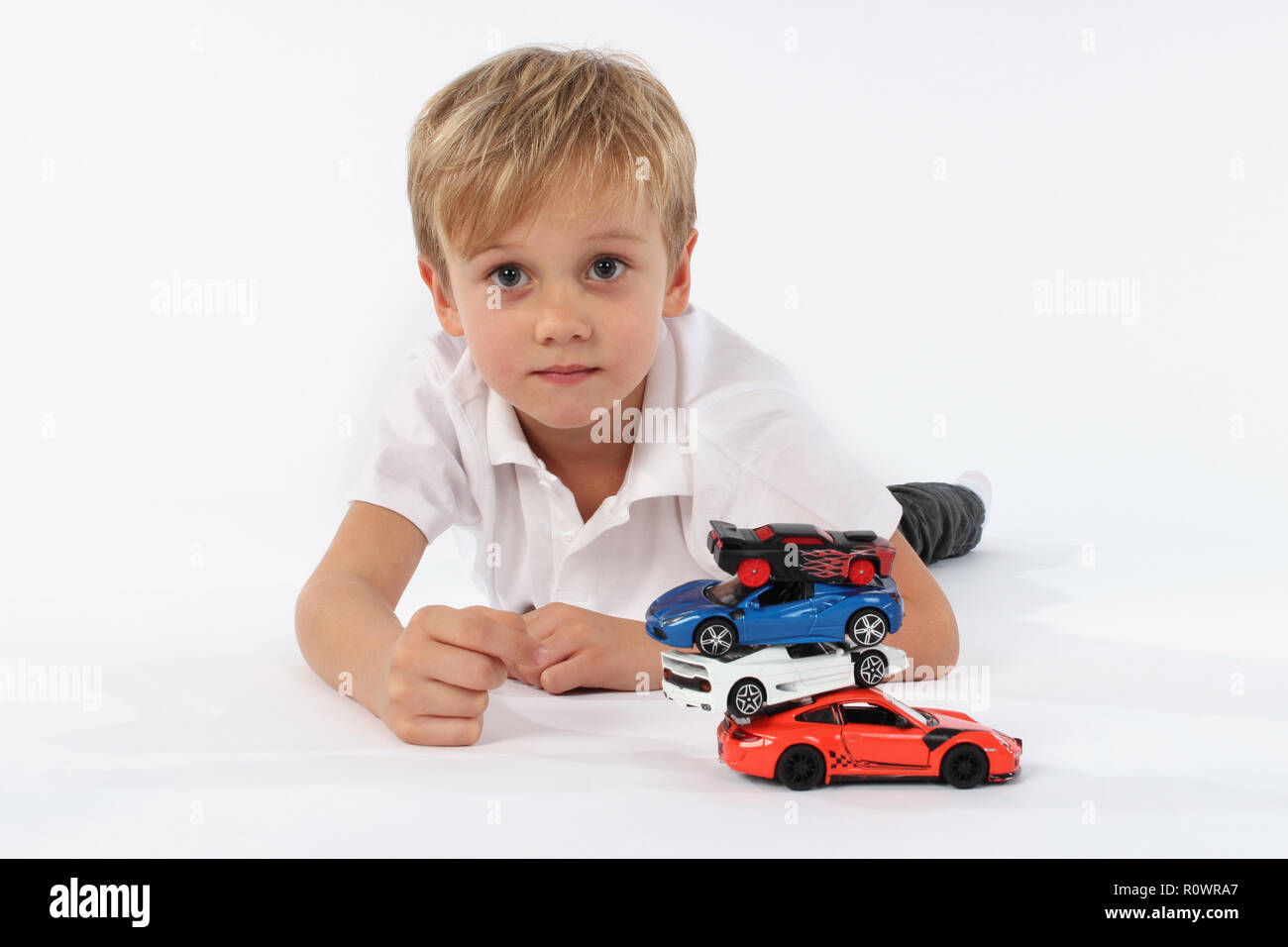 Child boy playing with toy cars in a studio - Stock Image