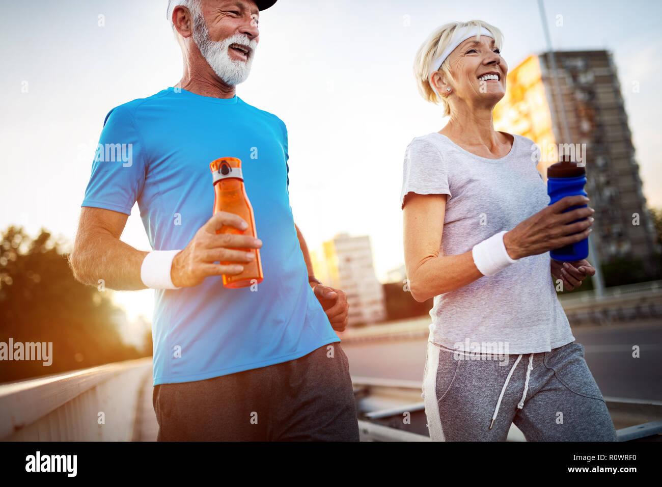Senior woman and man running doing fitness exercises Stock Photo