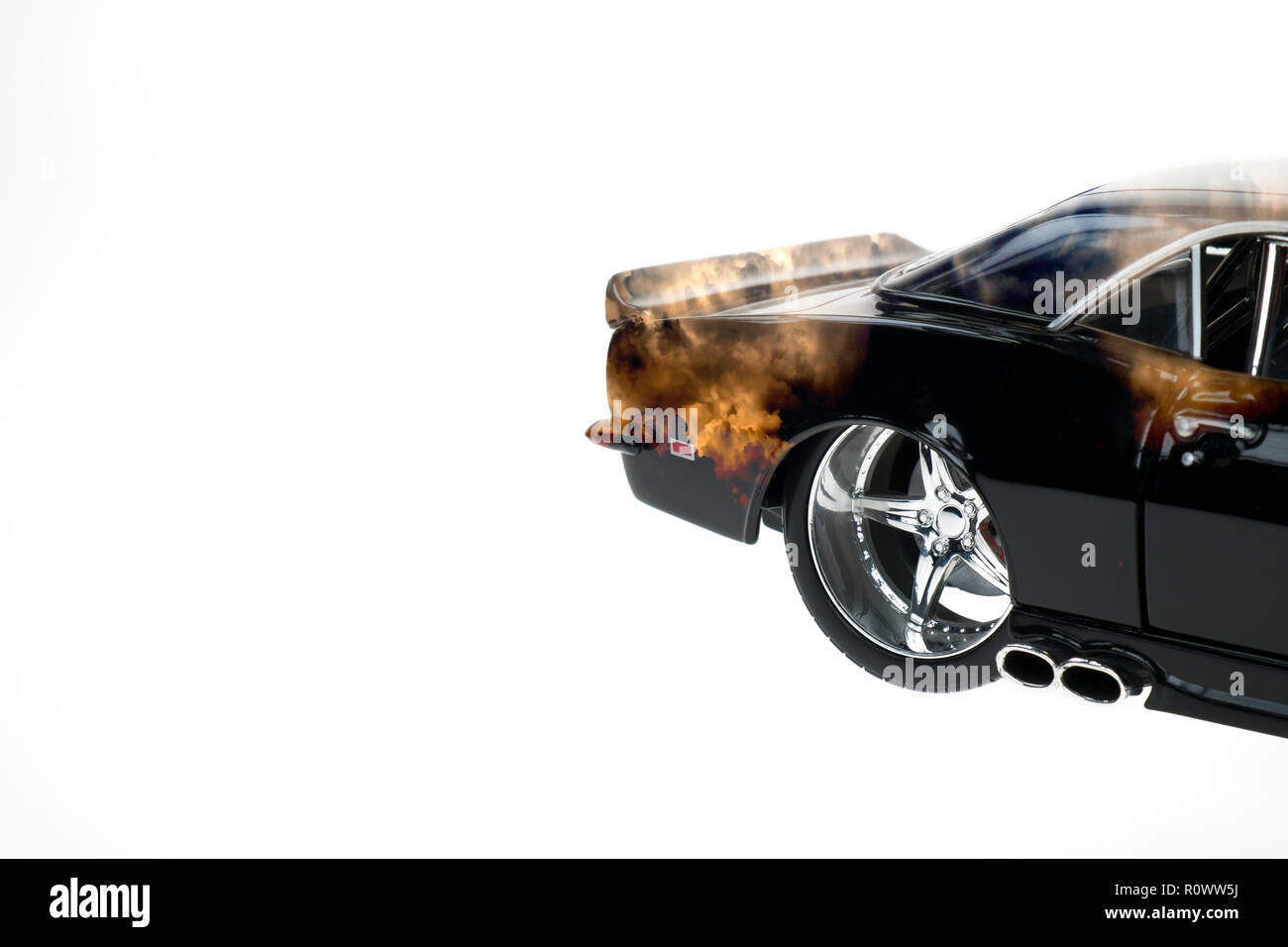 Rear view of a muscle diecast car double exposured with sunset clouds image on isolated white background Stock Photo