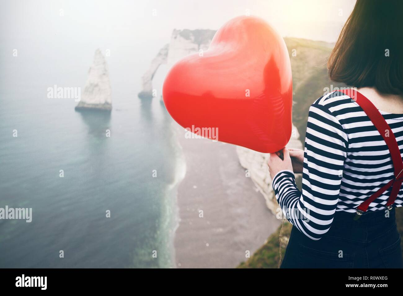 Happy girl with a red balloon in the shape of a heart at background of scenery Etretat. northern coast of France - Stock Image