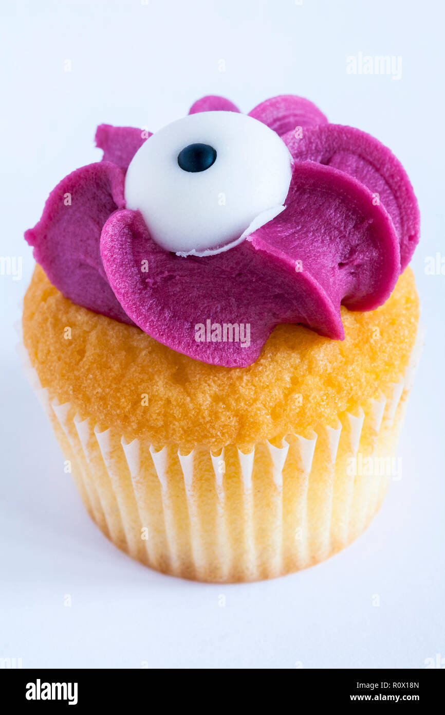 M&S mini monster cupcake blackcurrant cake finished with fondant icing eyeball for Halloween from mini monster cupcake selection on white background - Stock Image