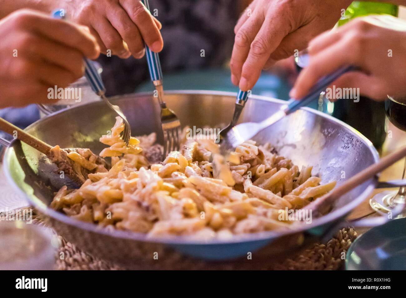 close up with different many hands friends taking italian pasta together with the forks to have fun and enjoy the friendship. Everybody eating with th - Stock Image