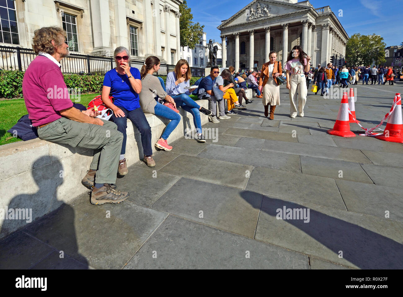 People relaxing at lunchtime in front of the National Gallery in Trafalgar Square, London, England, UK. - Stock Image