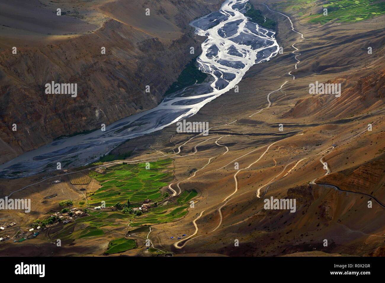 The Spiti River gleams silver in the golden hour. - Stock Image
