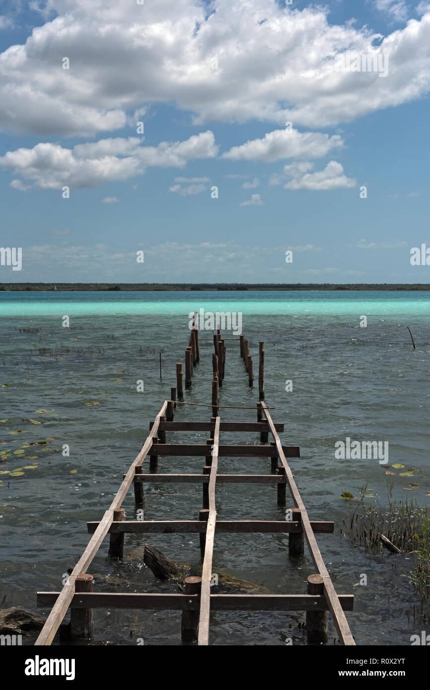 Old broken pier at the lagoon of Bacalar, Quintana Roo, Mexico. - Stock Image
