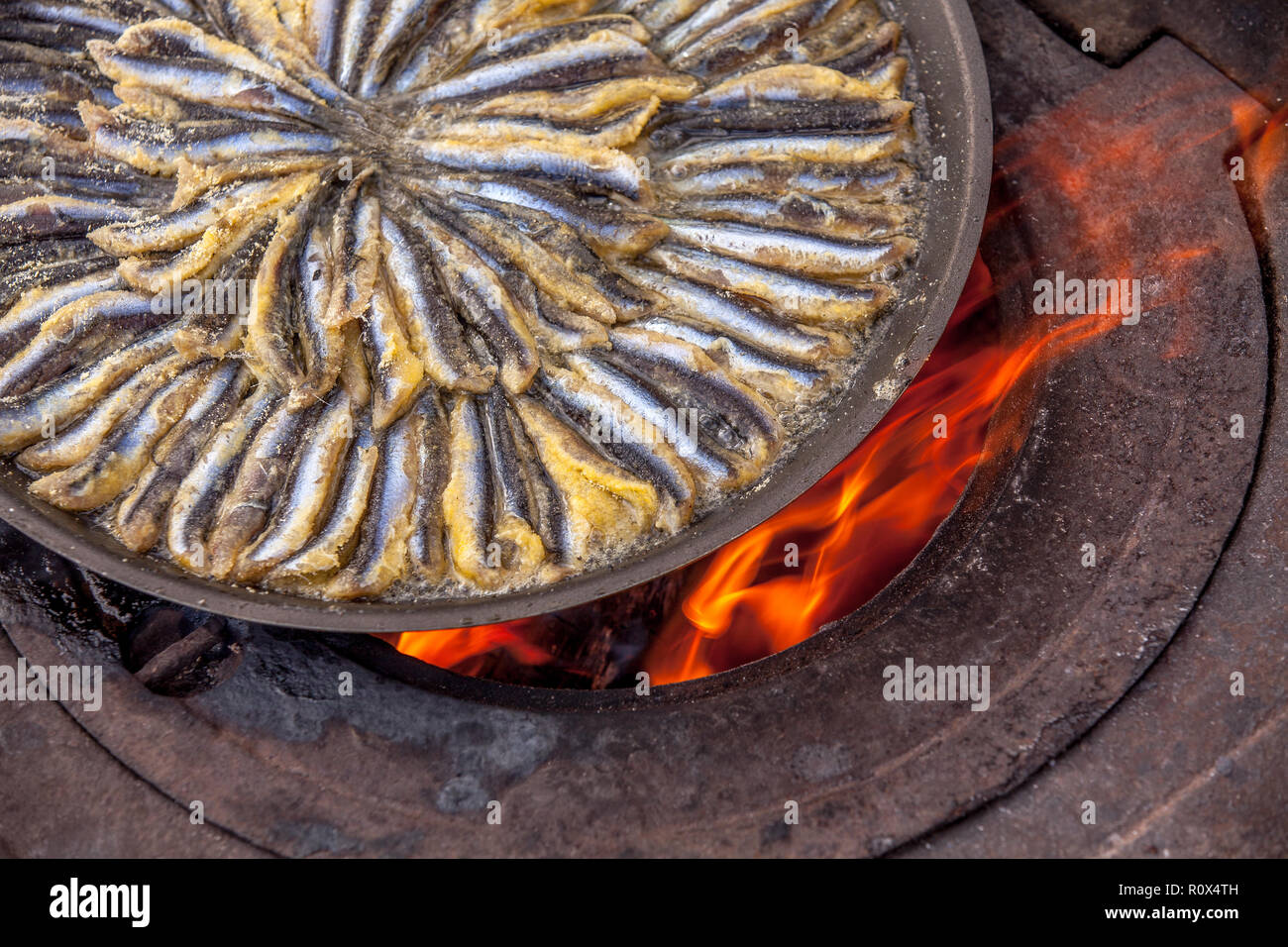 fish in frying pan, on old stove closeup - Stock Image