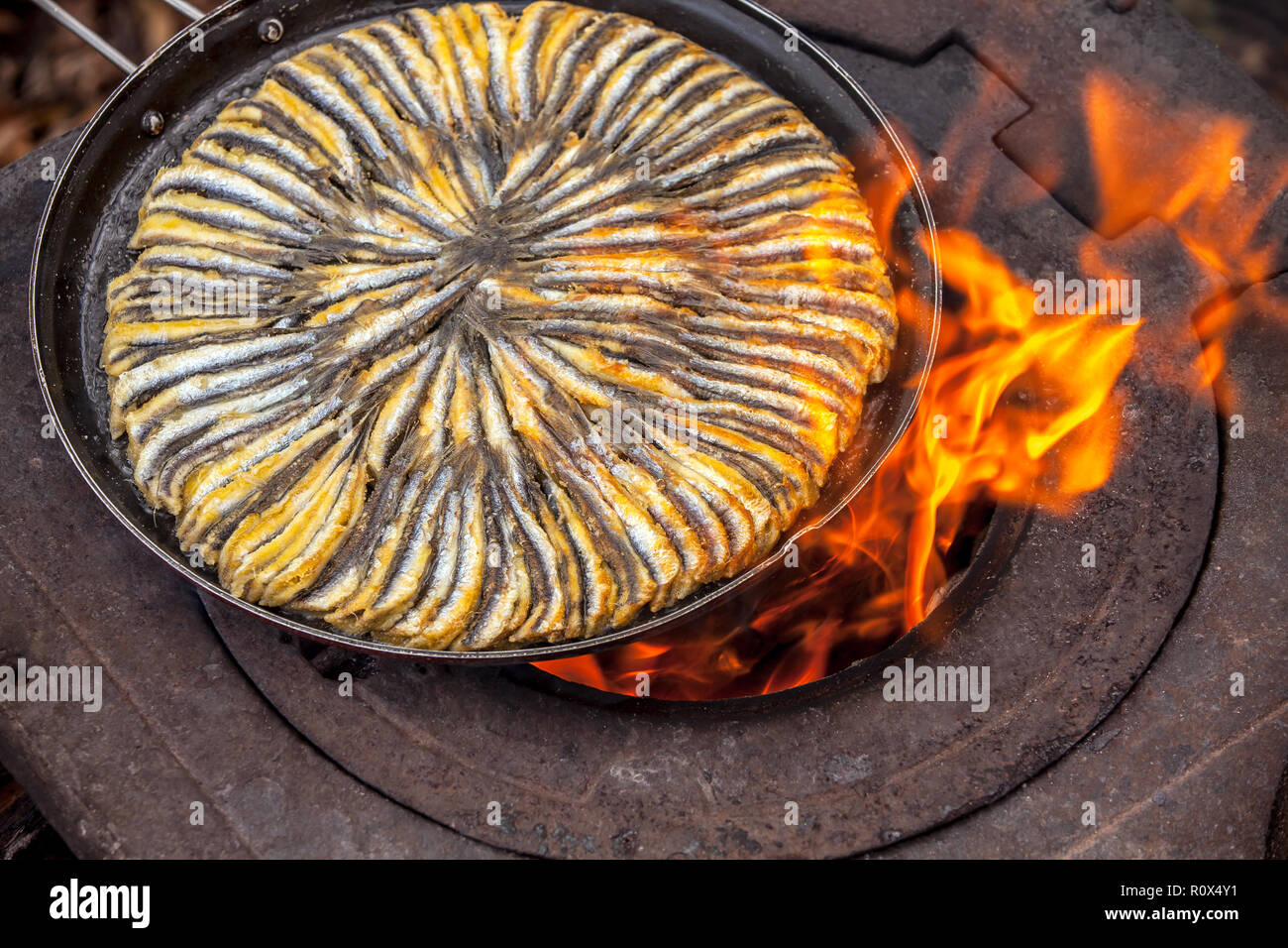 fish in frying pan, on old stove - Stock Image