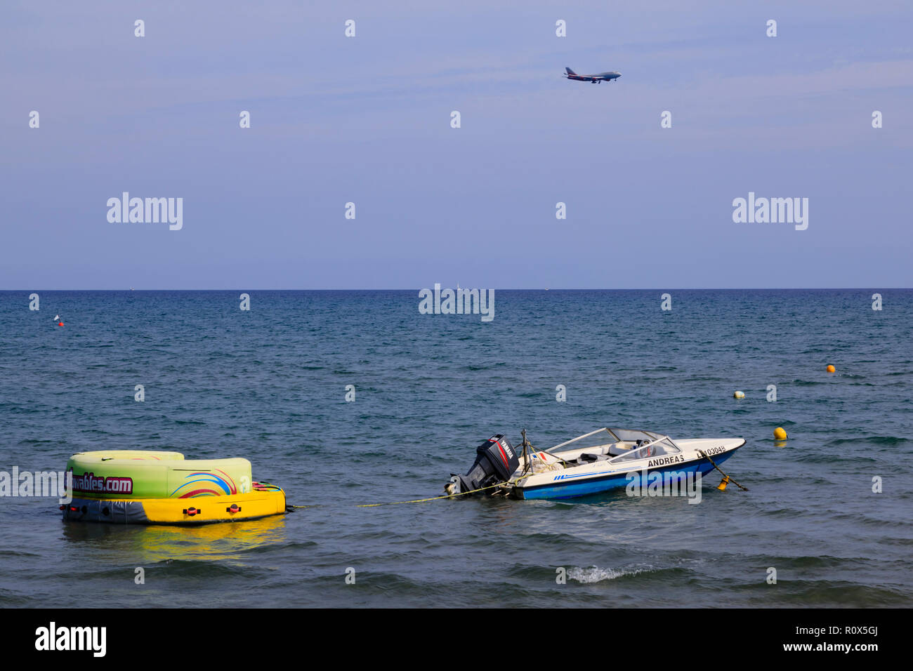 Airliner on approach to Glafcos Clerides International Airport, Larnaca, over boats anchored at Finikoudes beach, Cyprus October 2018 - Stock Image
