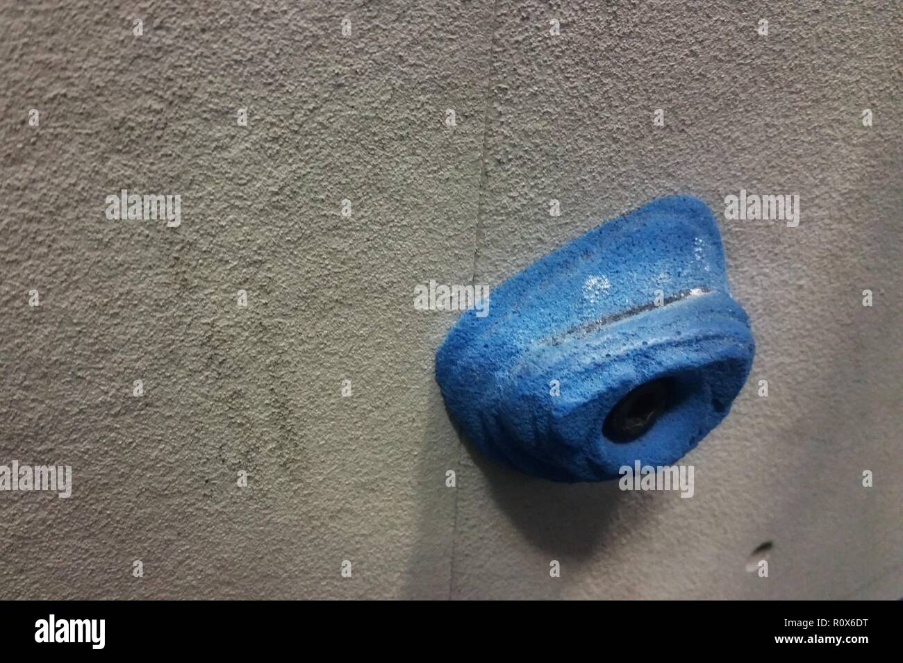 One blue rock climbing foothold against a grey wall - Stock Image