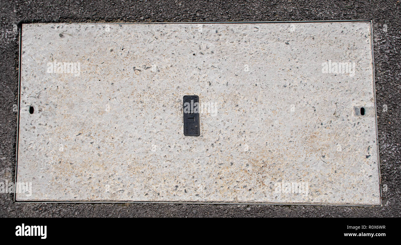 Basingstoke, United Kingdom - August 31 2018:   An access cover or manhole cover for access to British Telecom network in the pavements of Chineham pa - Stock Image