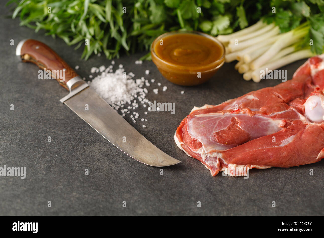 Raw lamb meat with spices on wood board over old wooden background. Close up, selective focus. - Stock Image