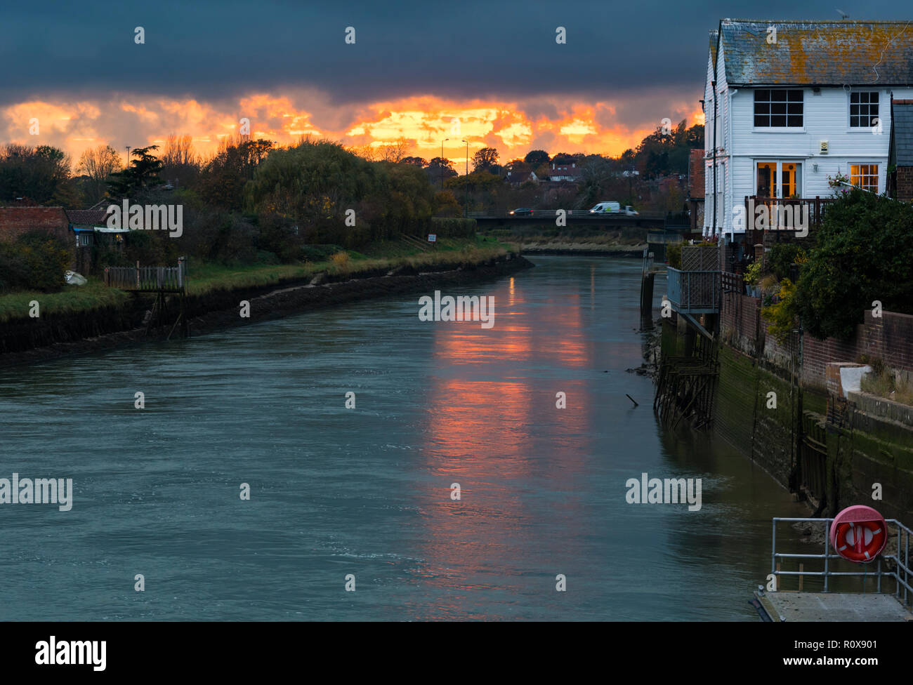 Sun going down in Autumn over the River Arun with riverside houses in Arundel, West Sussex, England, UK. Stock Photo