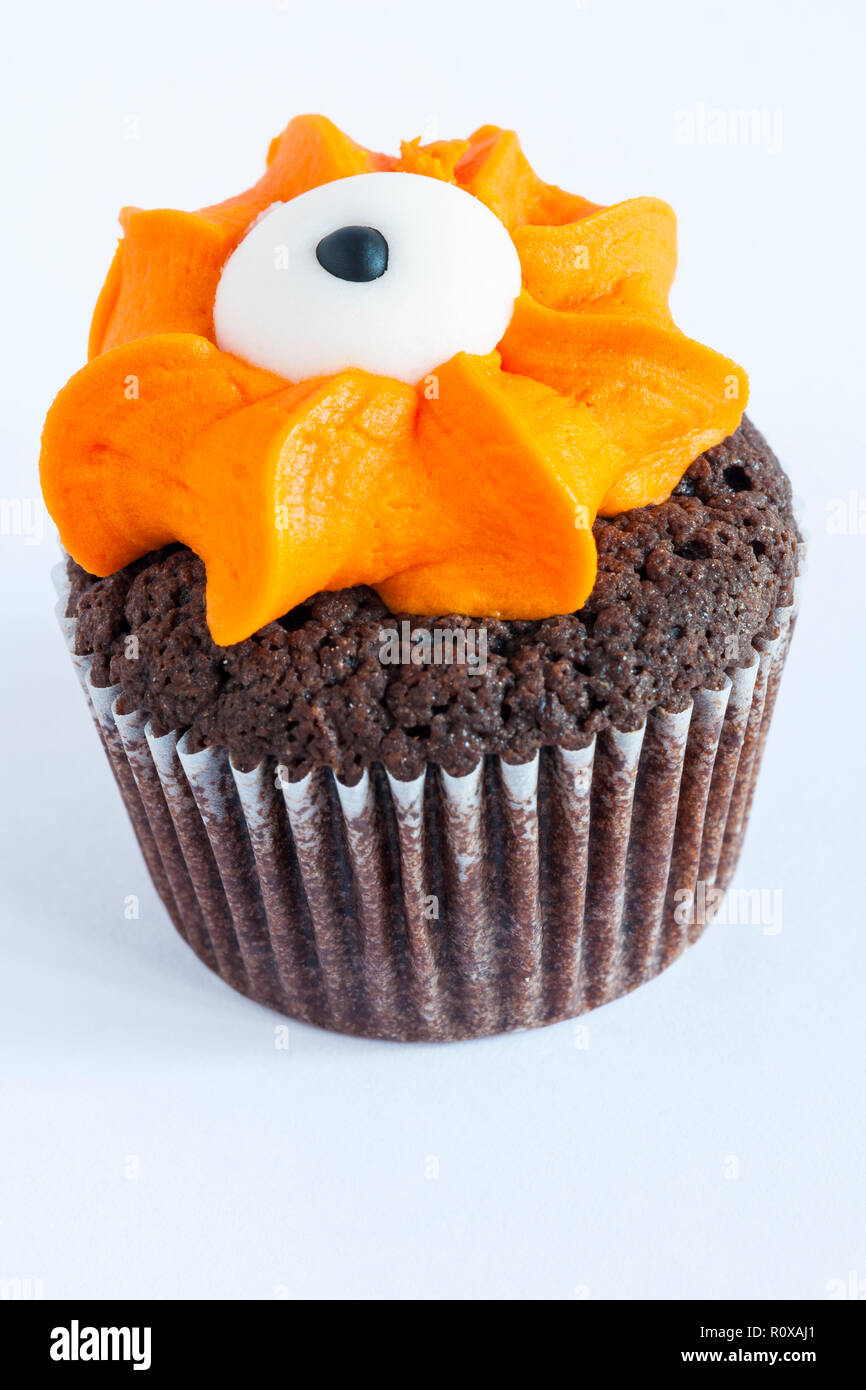 M&S mini monster cupcake chocolate & orange cake finished with fondant icing eyeball isolated on white background from mini monster cupcake selection - Stock Image