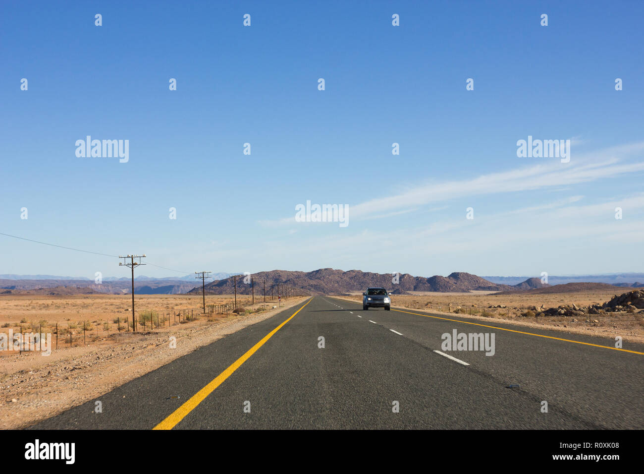 passenger vehicle on tarred national road in African dry and arid landscape on the Cape Namibia route - Stock Image