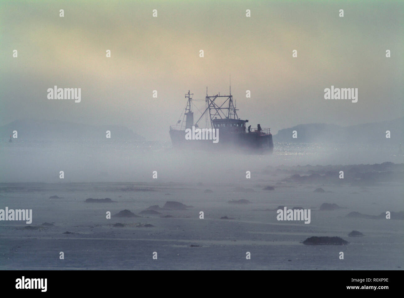 A scallop dredger navigates the channel up the River Dee to Kirkcudbrifght Harbour in thick fog. The tide is low and the channel is narrow and shallow - Stock Image