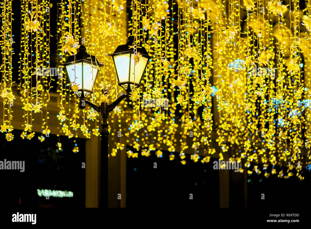 Metal lantern on background of shiny neon garland, night, city street. Fall, fest backdrop. Festive occasions concept, holiday, Christmas, New Year backdrop - Stock Image