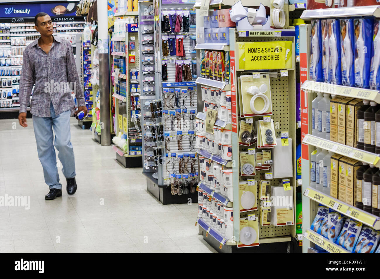 Miami Beach Florida Walgreens pharmacy drugstore retail chain business product display aisle shelf Black man shopping - Stock Image