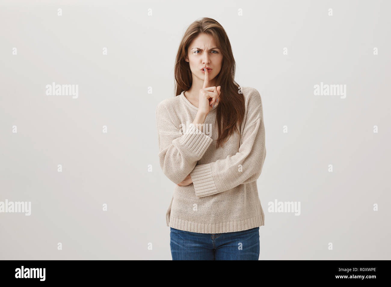 Keep it down, why you have to be so disgusting. Studio shot of angry irritated caucasian female frowning and being in bad temper showing shh sign, saying shush to demand lower voice and be silent - Stock Image