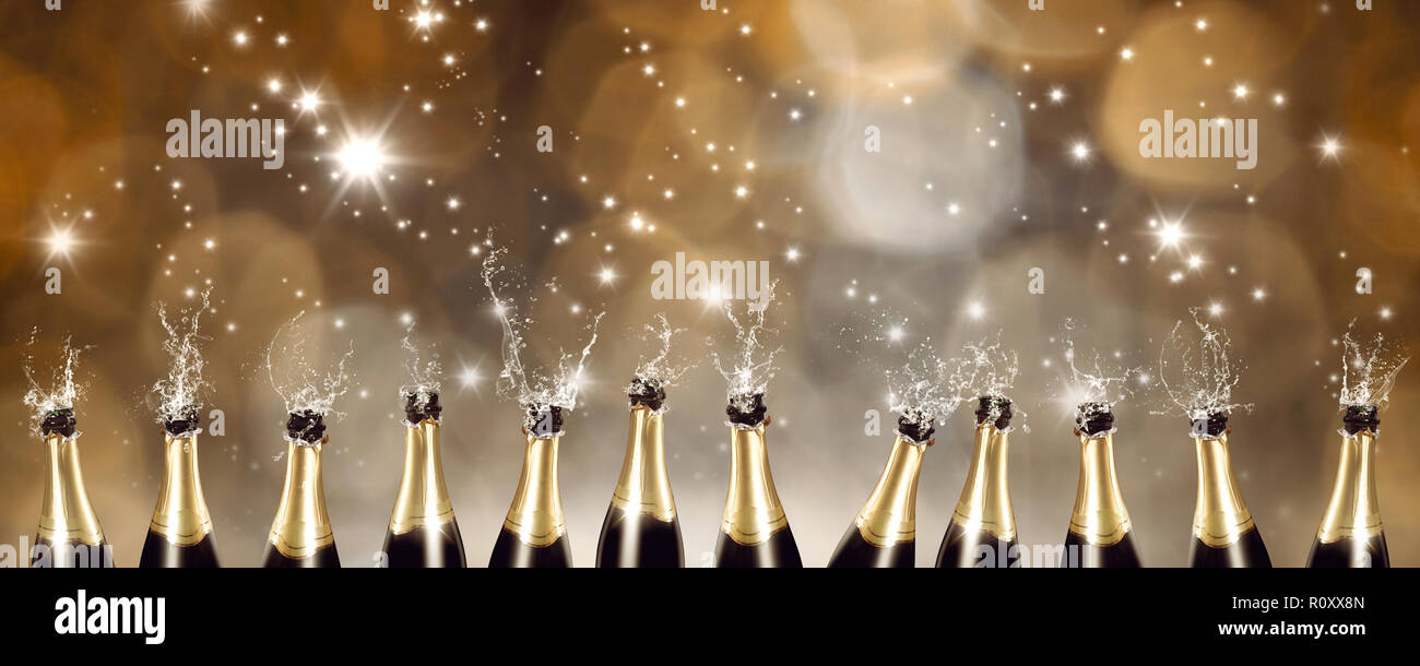 Splashing Champagne bottles with blurred lights in the background Stock Photo
