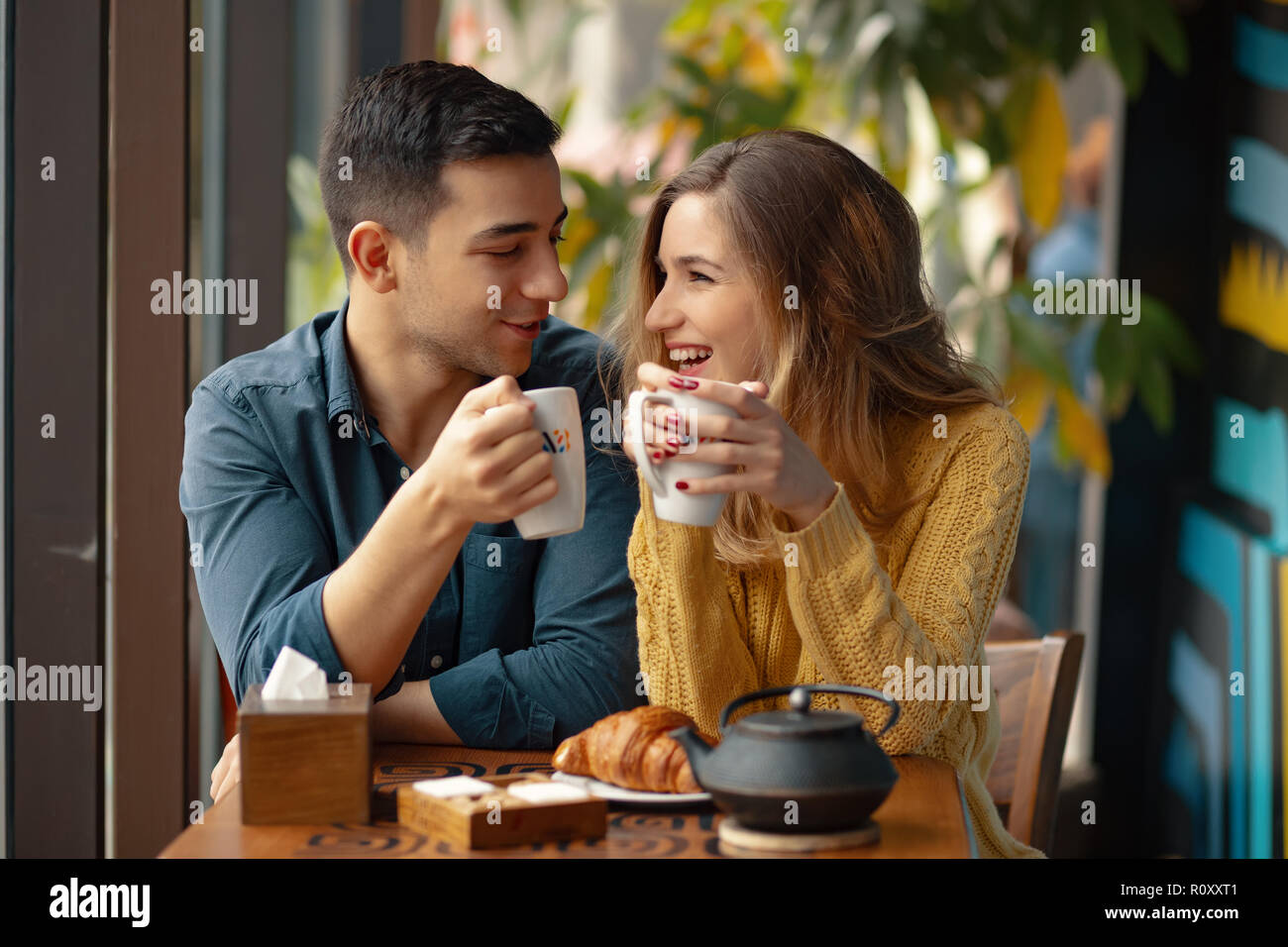 Young attractive couple on date in coffee shop having a conversation and enjoying the time spent with each other. Stock Photo