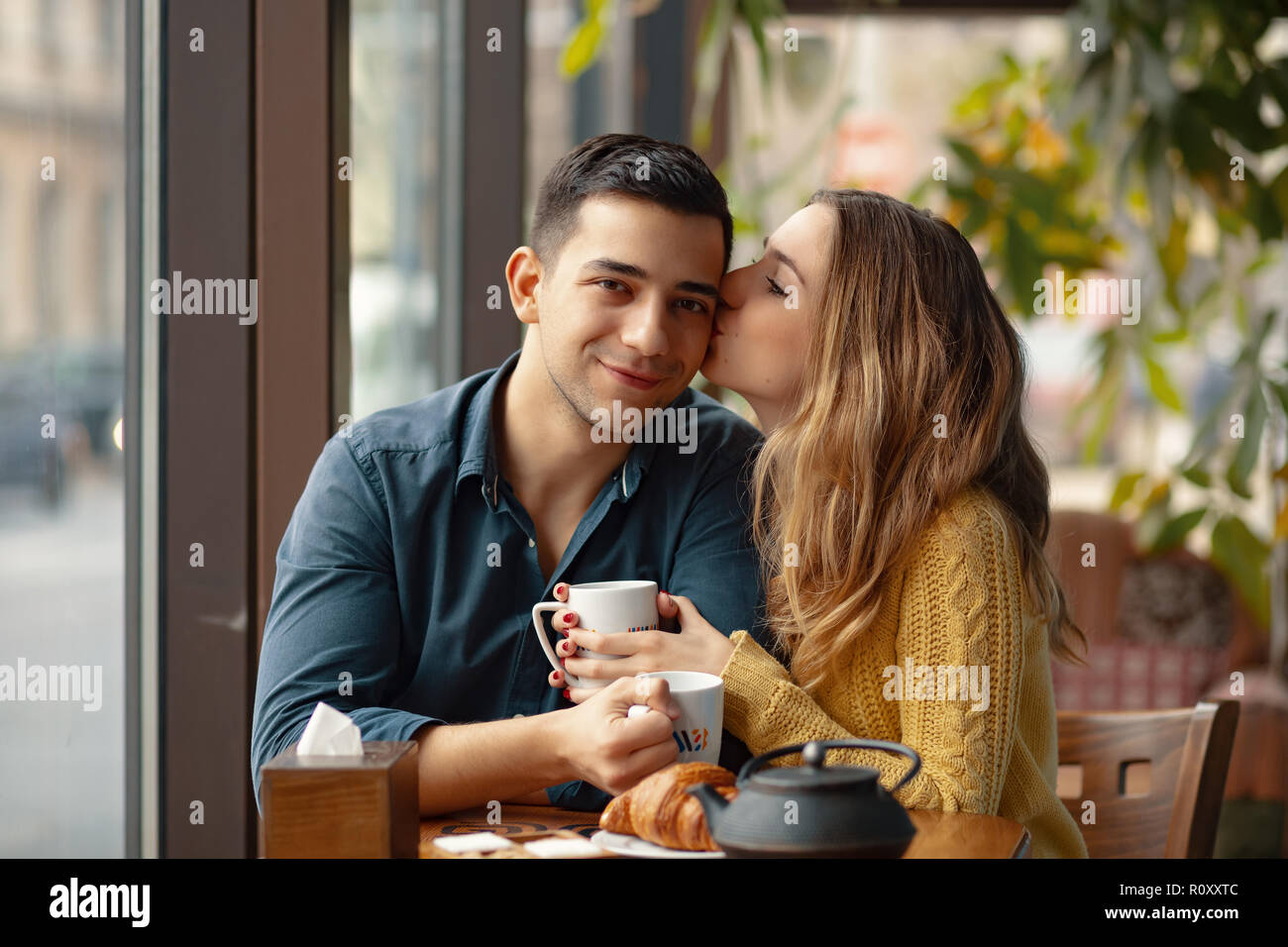 Young attractive couple on date in coffee shop. Woman kissing her men on the cheek with affection Stock Photo - Alamy