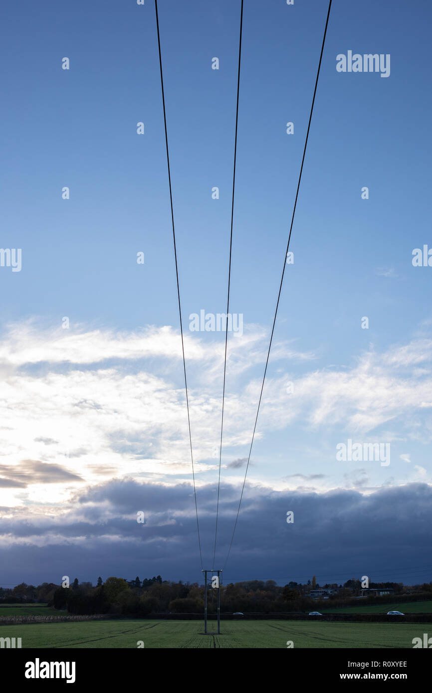 A silhouette of a powerline, with cloudy sky in the field near Swindon Village in Cheltenham, Gloucestershire, United Kingdom. - Stock Image
