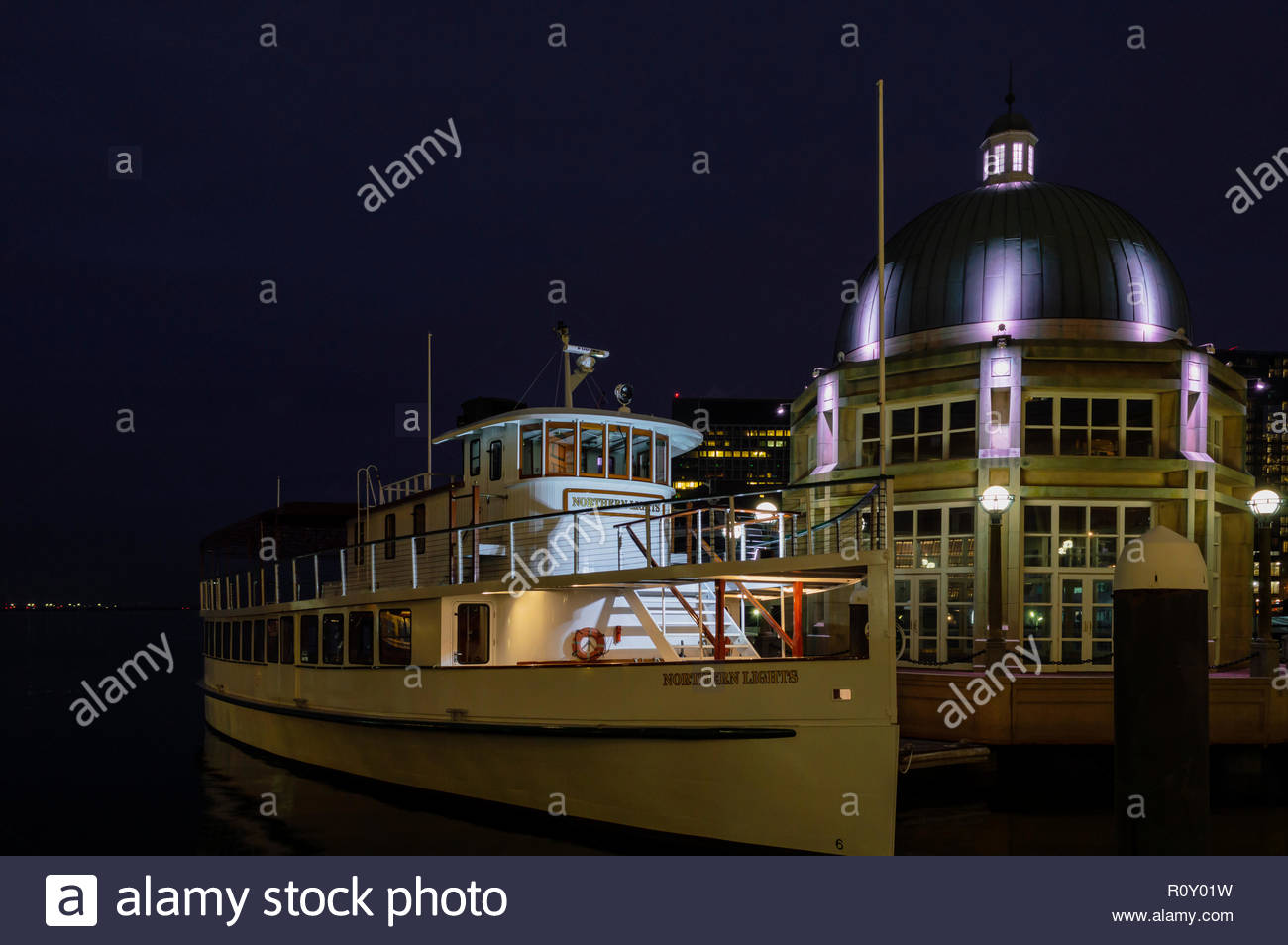 Boston, Massachusetts, USA - January 19, 2017: Foredeck of classically styled cruiser Northern Lights glowing in pre-dawn winter darkness at Rowes Wha - Stock Image