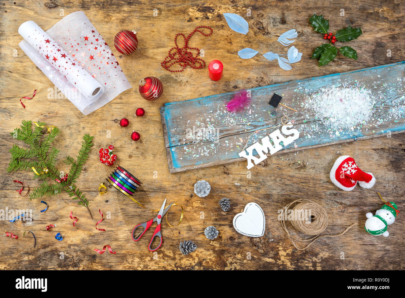 Accessories, Preparing for Christmas. Holiday decoration toys, garlands, lights, wreath over old vintage wooden table ,top view Stock Photo