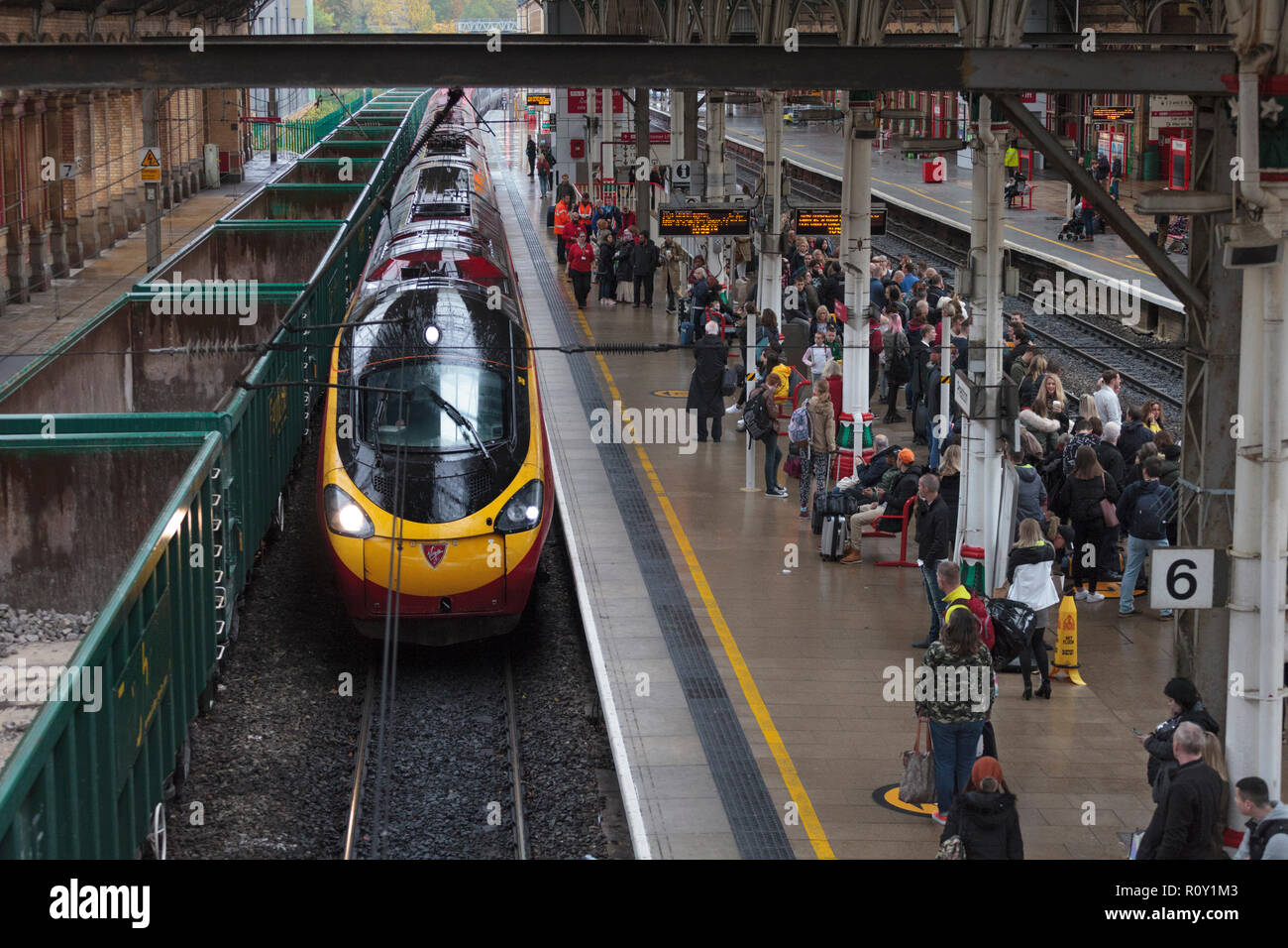 A Virgin trains pedolino train arriving at a wet Preston railway station alongside a crowded platform - Stock Image