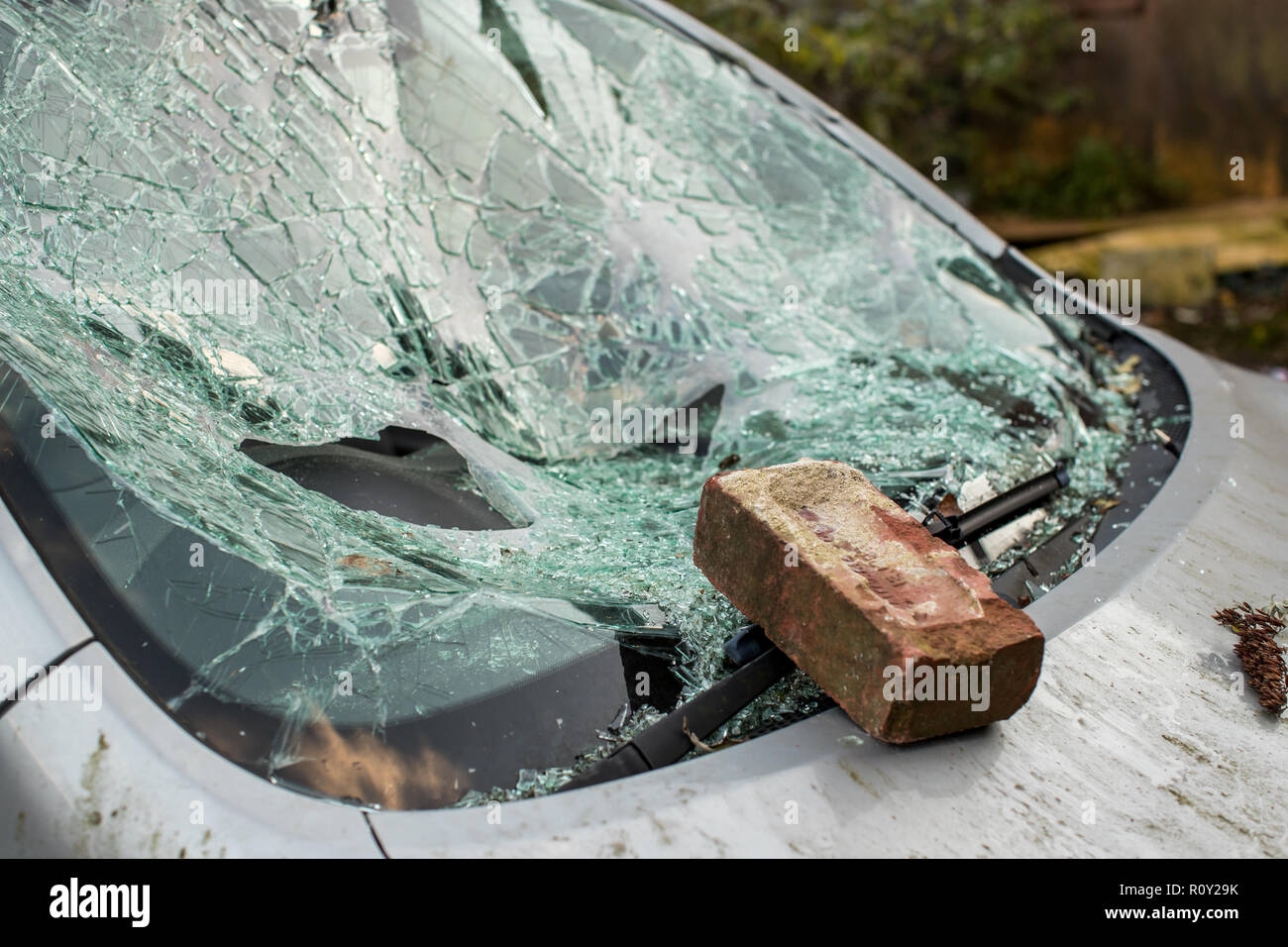 Brick sits on smashed windshield of a car with broken glass everywhere.  The car has been broken into and stolen. Car crime is a problem in United Kin - Stock Image