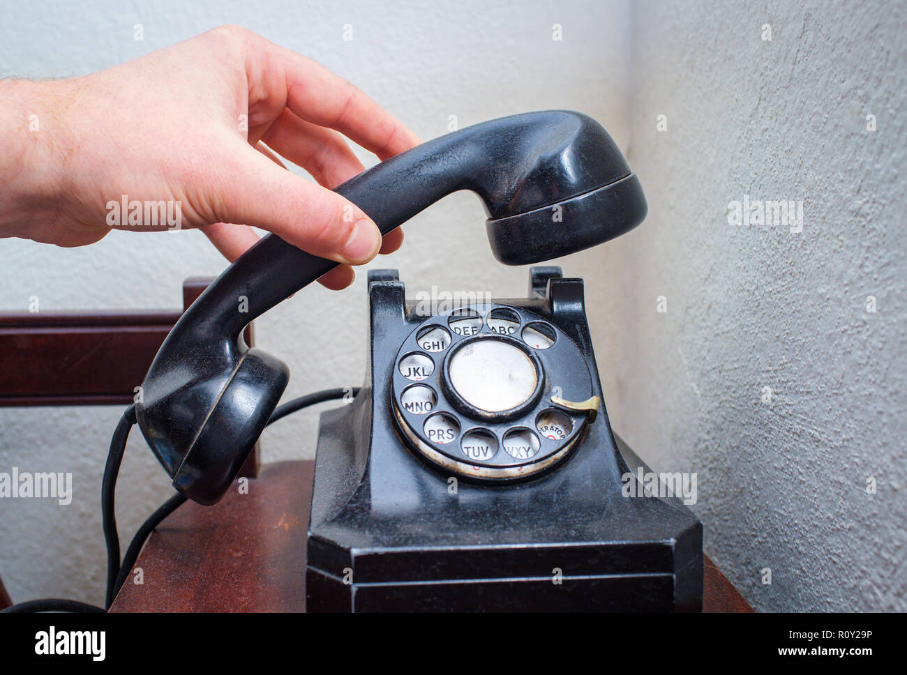 Old vintage rotary dial telephone on wooden desk - Stock Image
