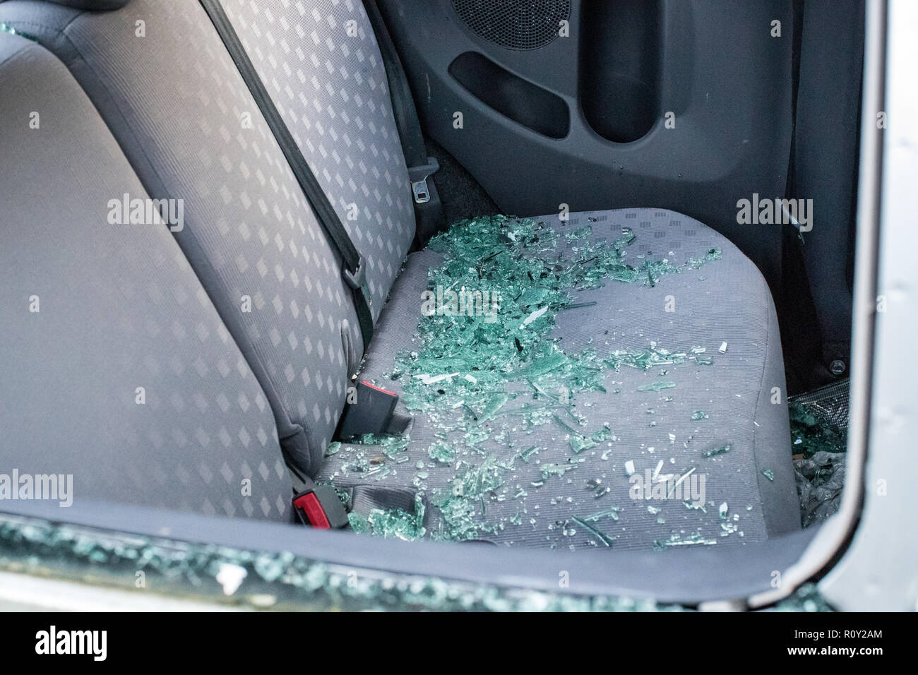 The back seat of a vandalized car with broken smashed glass covering the seat.  The car was broken into and stolen. - Stock Image