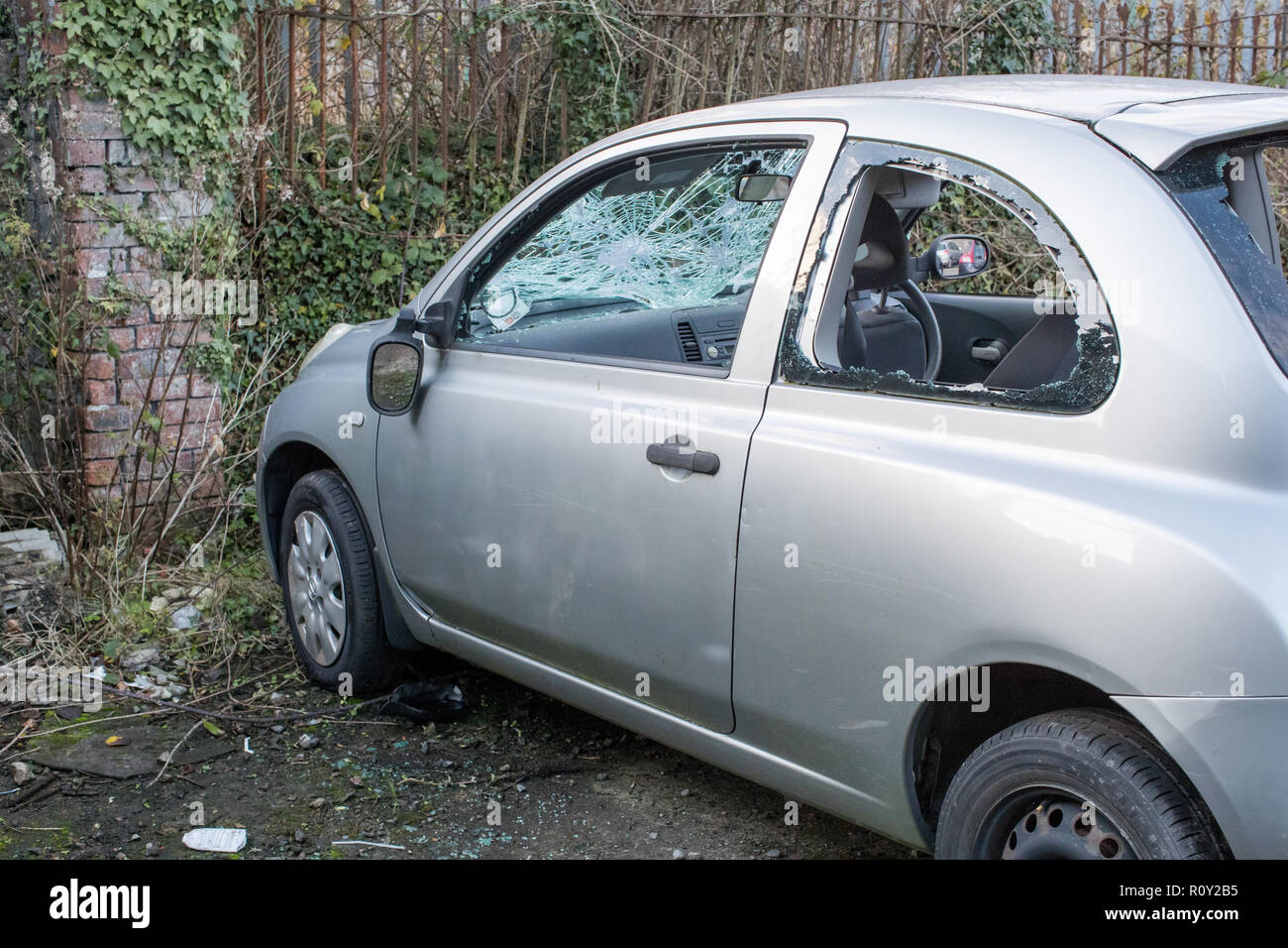 Dumped on the street a stolen car is left vandalised and broken with smashed glass and the wing mirror hanging off. - Stock Image