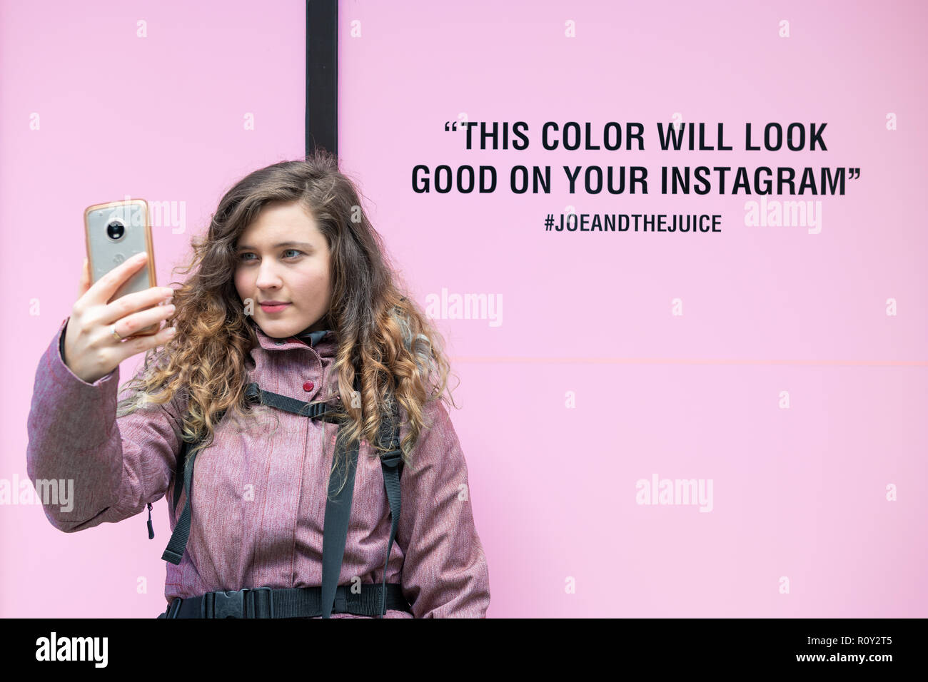 Washington DC, USA - March 9, 2018: Young woman taking selfie against millennial pink color background outside, outdoors in cold winter, dressed in co - Stock Image
