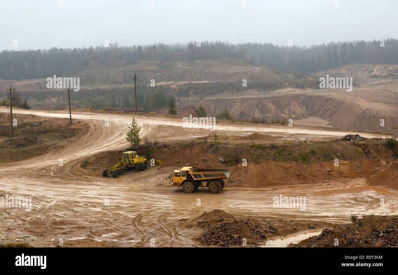 Top view panorama of deep kaolin strip mine with dumper trucks and cranes. Quarry for the extraction of minerals. The work of construction equipment i Stock Photo