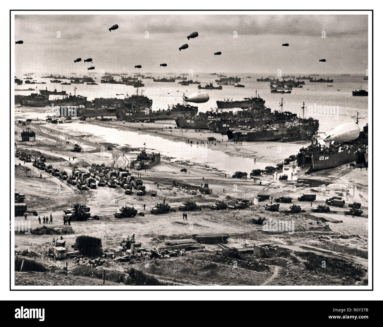 OMAHA BEACH D-Day Normandy WW2 B&W image D Day Plus 1 LCT landing craft tank with barrage balloons afloat, unloading supplies on Omaha for the break-out from Normandy. June 1944 Stock Photo